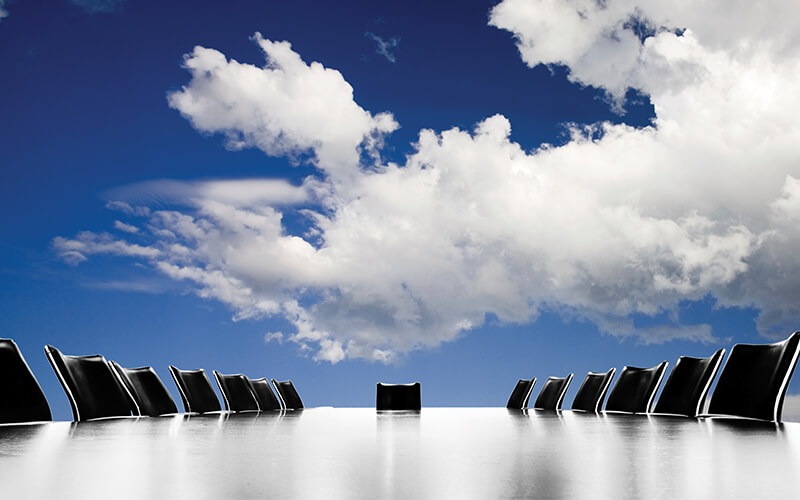 Photo of a large board room table with empty chairs and a cloud filled sky above it.