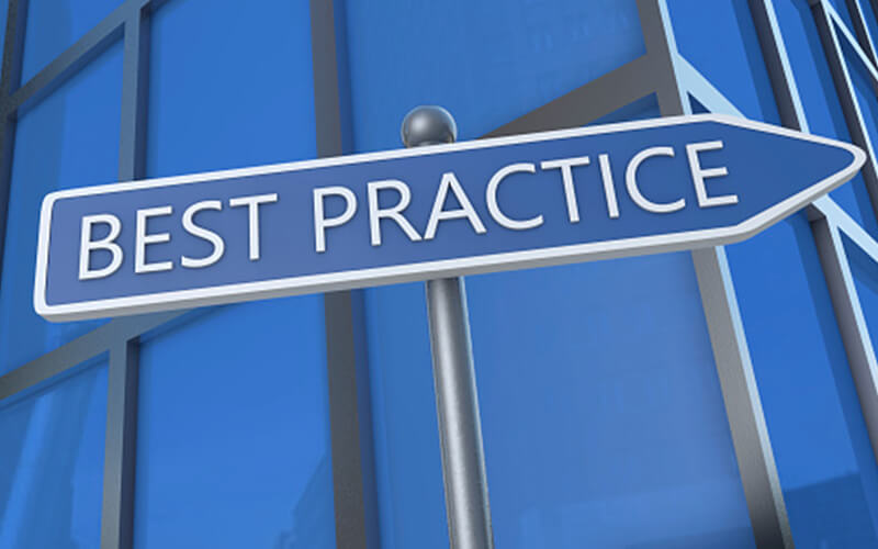 Image of a street sign with the words BEST PRACTICE on it, in front of an office building.